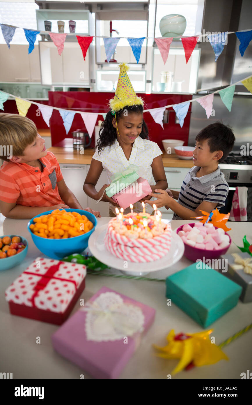 Boy Giving Birthday Present To His Sister In Kitchen At Home
