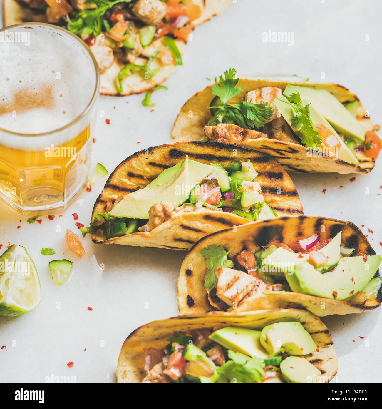 Healthy corn tortillas with grilled chicken, avocado, fresh salsa, limes, beer in glass over light grey marble background, - Stock Image