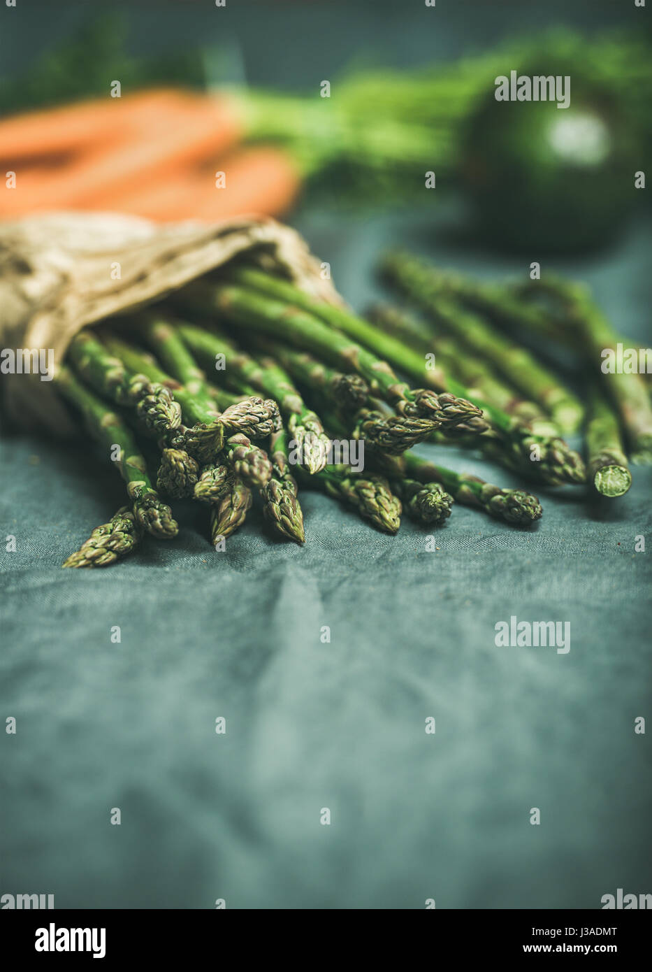 Fresh seasonal vegetables on table. Green asparagus, carrots and avocado at background over grey linen table cloth. - Stock Image