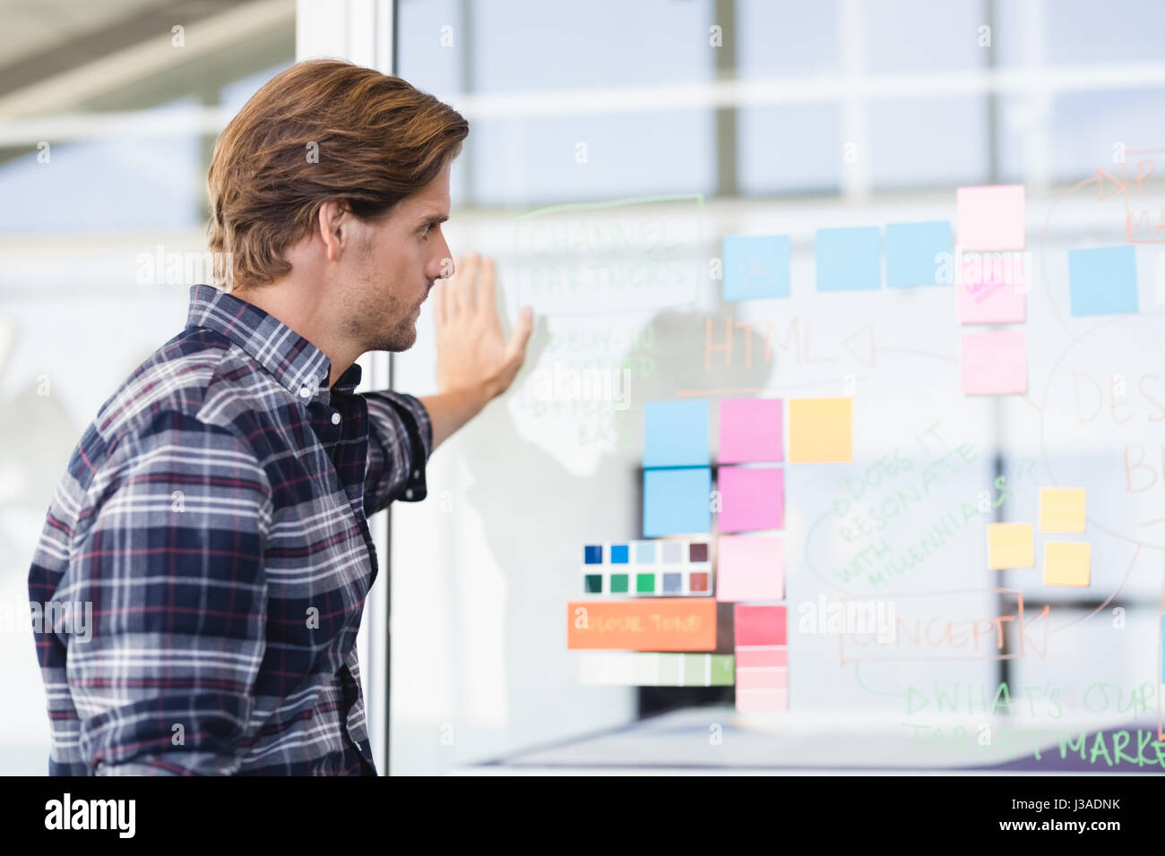 Businessman looking at plan on glass wall in office - Stock Image