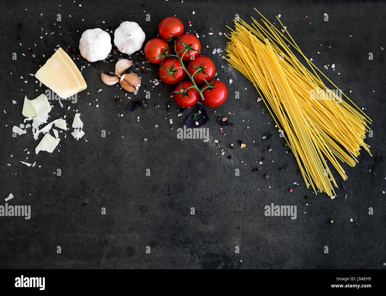 Food frame. Pasta ingredients. Cherry-tomatoes, spaghetti pasta, garlic, basil, parmesan and spices on dark grunge - Stock Image