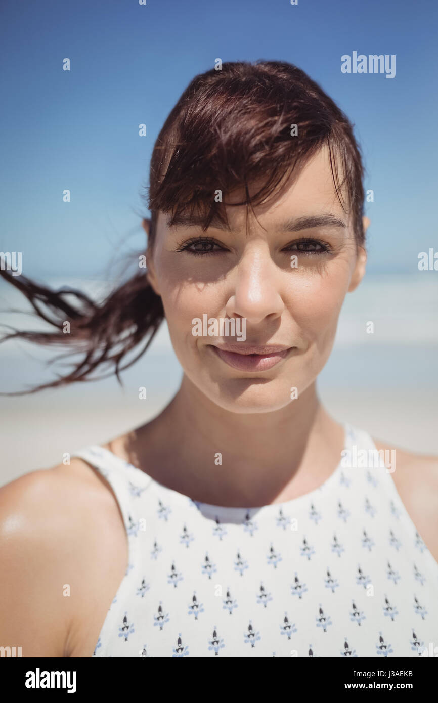 Portrait of young woman with tousled hair standing at beach during sunny day - Stock Image