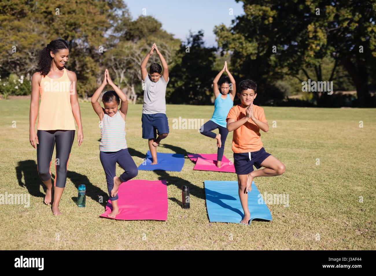 Trainer looking at children practicing Vriksasana at park Stock Photo