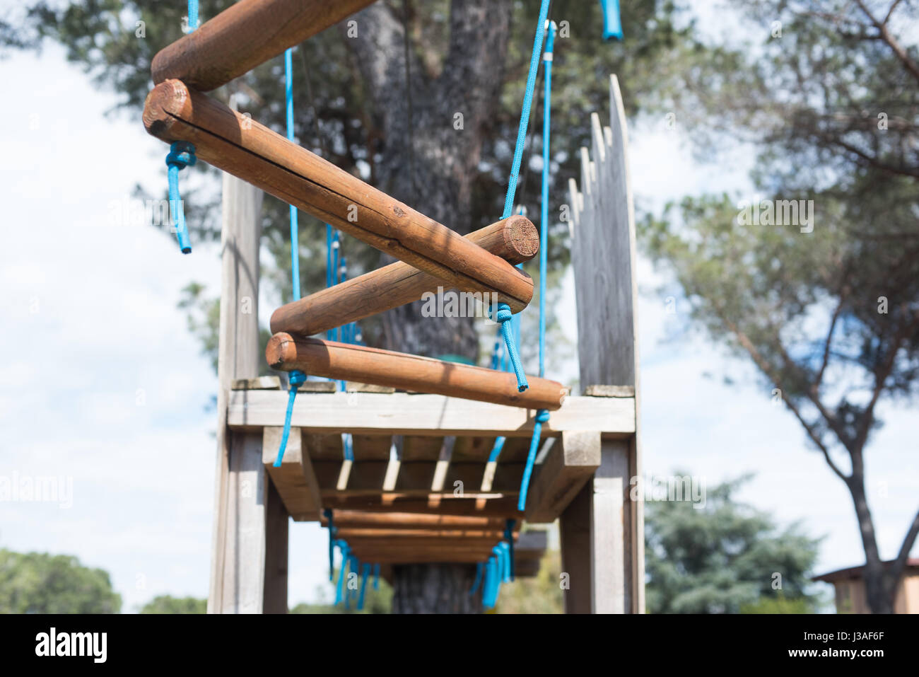 Adventure playground suspended test path, selective focus obstacle in foreground - Stock Image