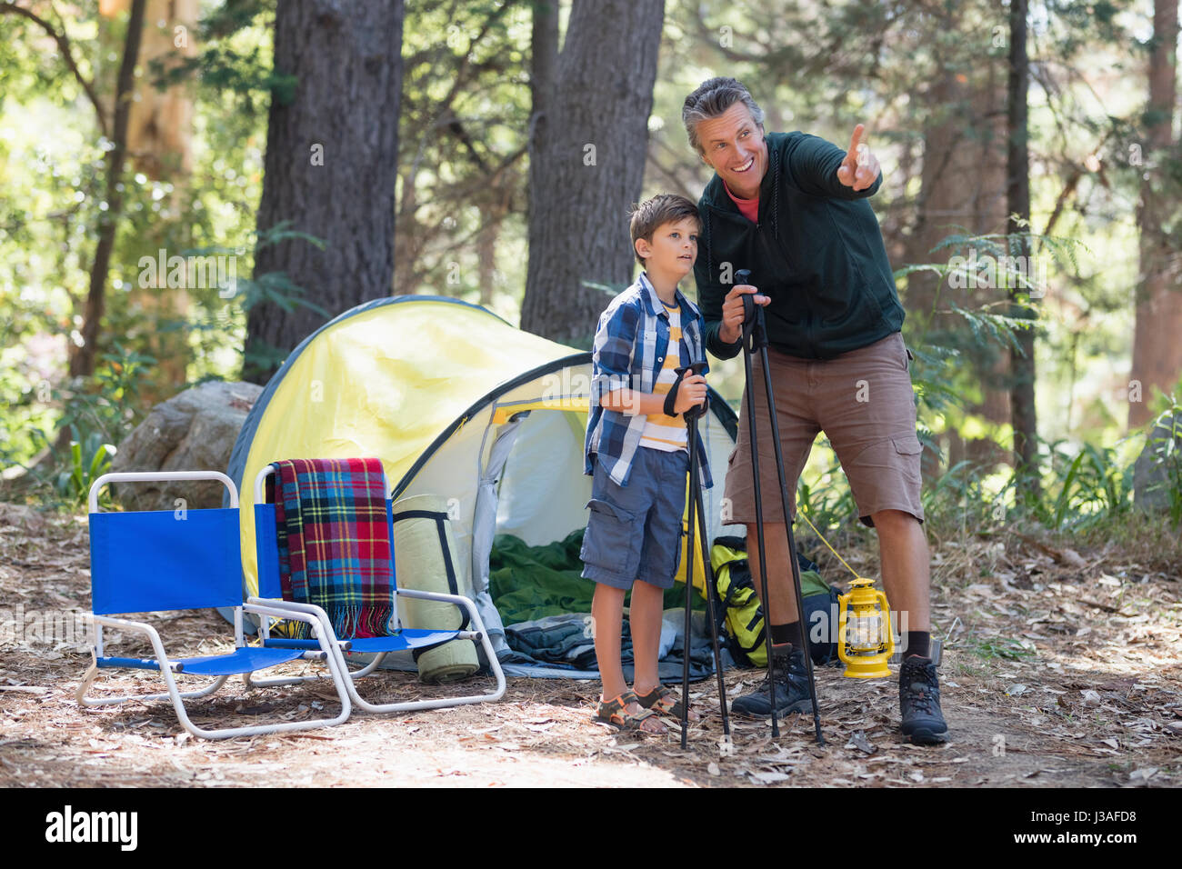Father showing something to son while hiking in forest - Stock Image