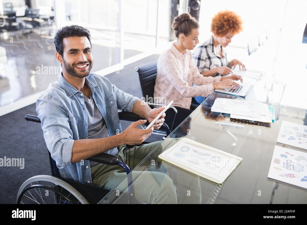 High angle portrait of smiling businessman using digital tablet while sitting on wheelchair at creative office - Stock Image