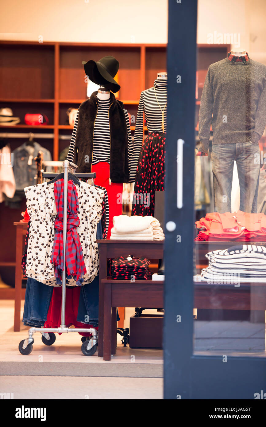 Interior of small retail stores with an open door and a number of dressed mannequins with clothing and personal - Stock Image