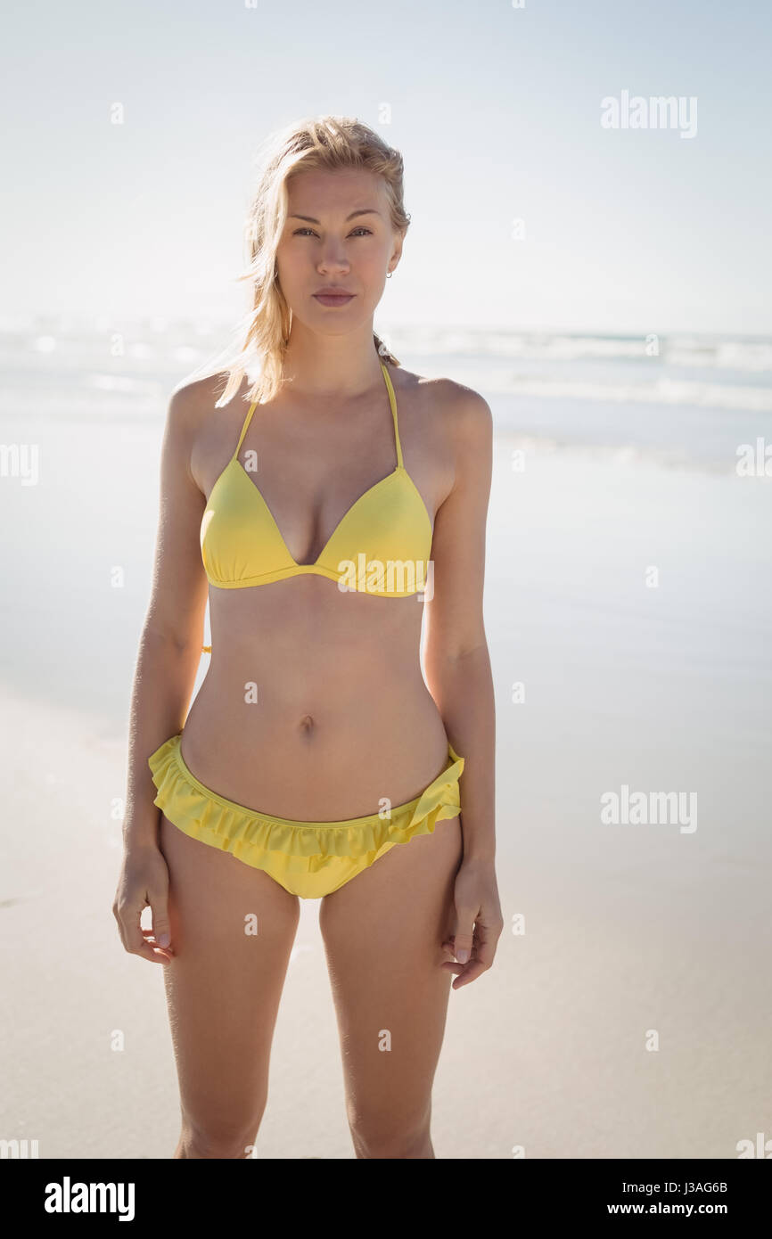 Portrait of young woman in yellow bikini standing at beach during sunny day - Stock Image