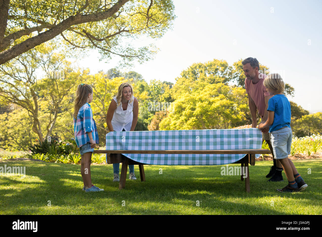 Family Spreading The Tablecloth On Picnic Table In Park