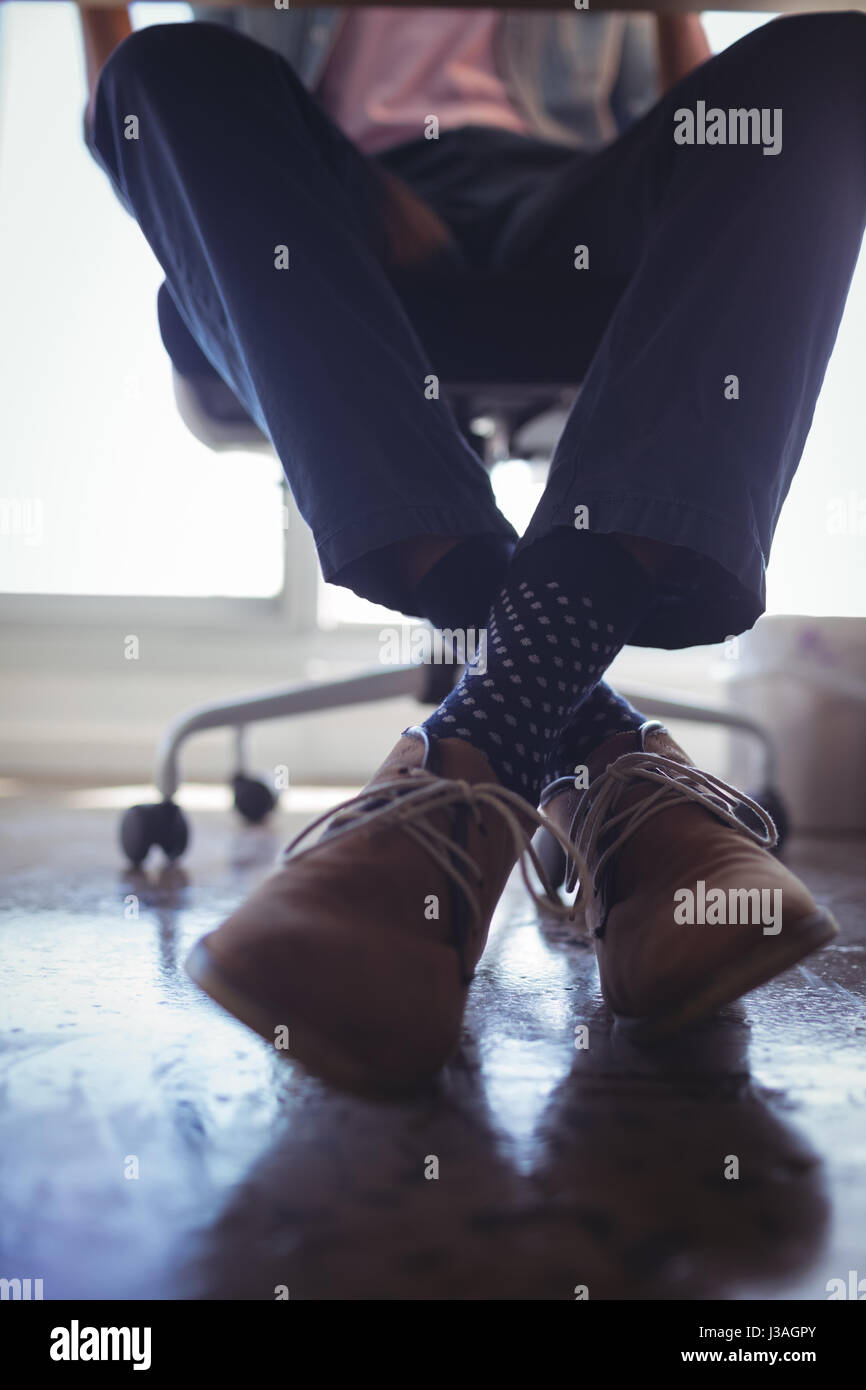 Low section of businessman wearing brown shoes while sitting on chair at office - Stock Image