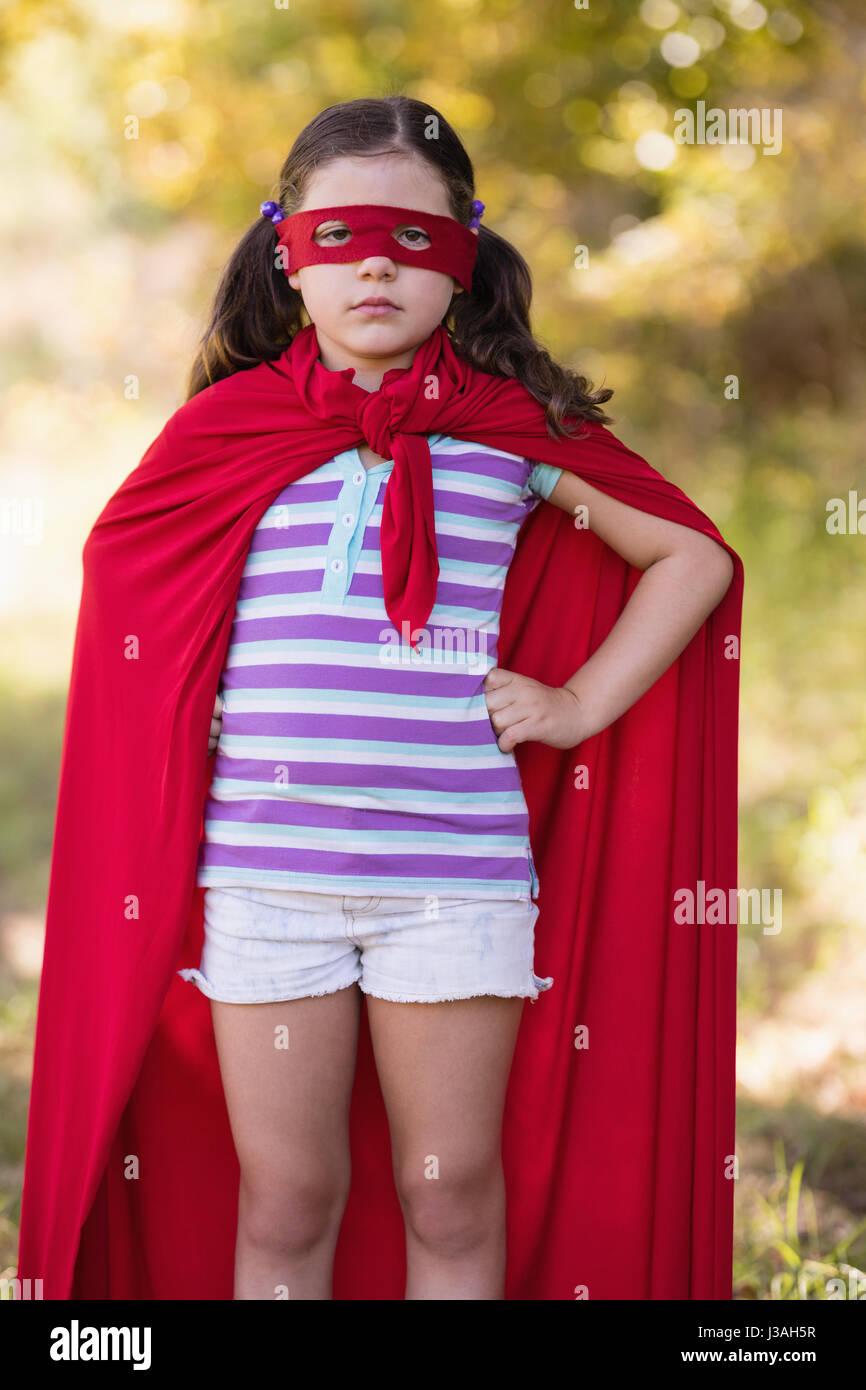 Portrait of confident little girl wearing superhero costume at campsite Stock Photo