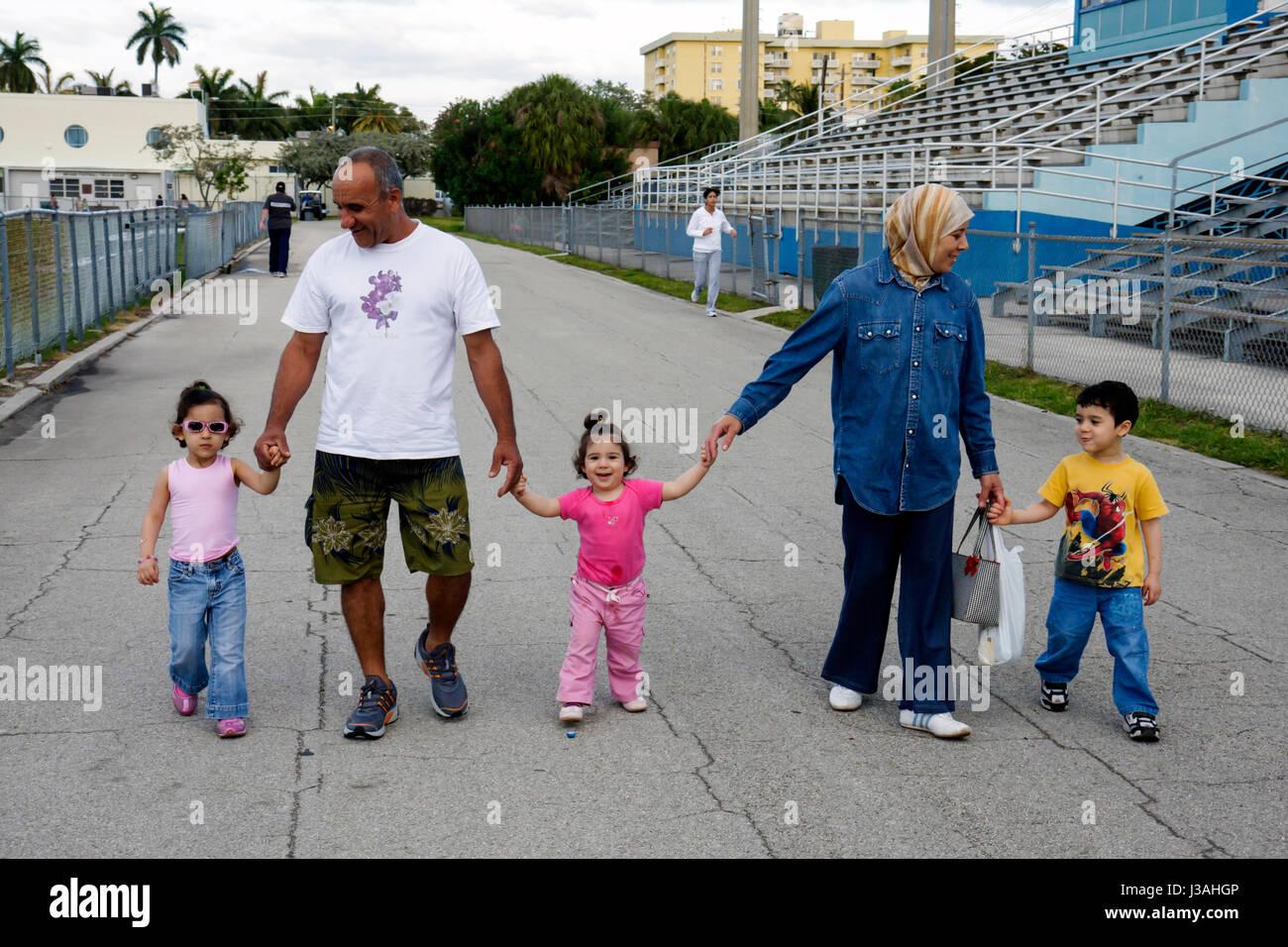 Miami Beach Florida Flamingo Park Muslim family man woman boy girls toddler preschooler walk exercise health ethnic - Stock Image