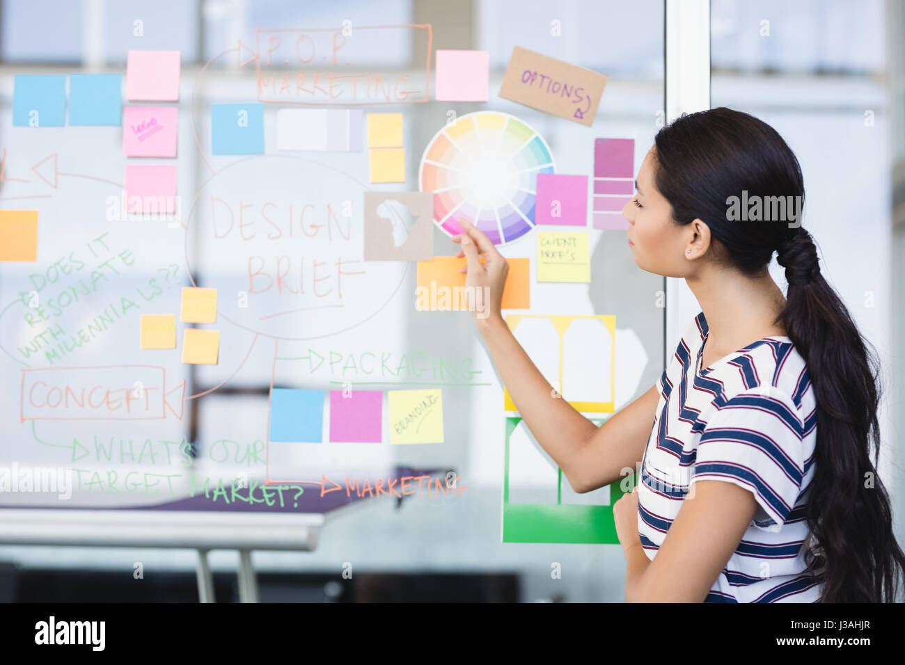 Businesswoman looking at plan on glass wall in office - Stock Image