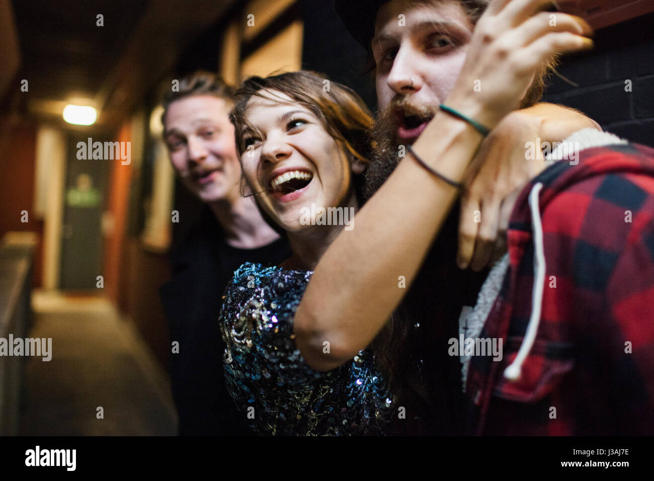 Smiling young woman embracing a friend - Stock Image