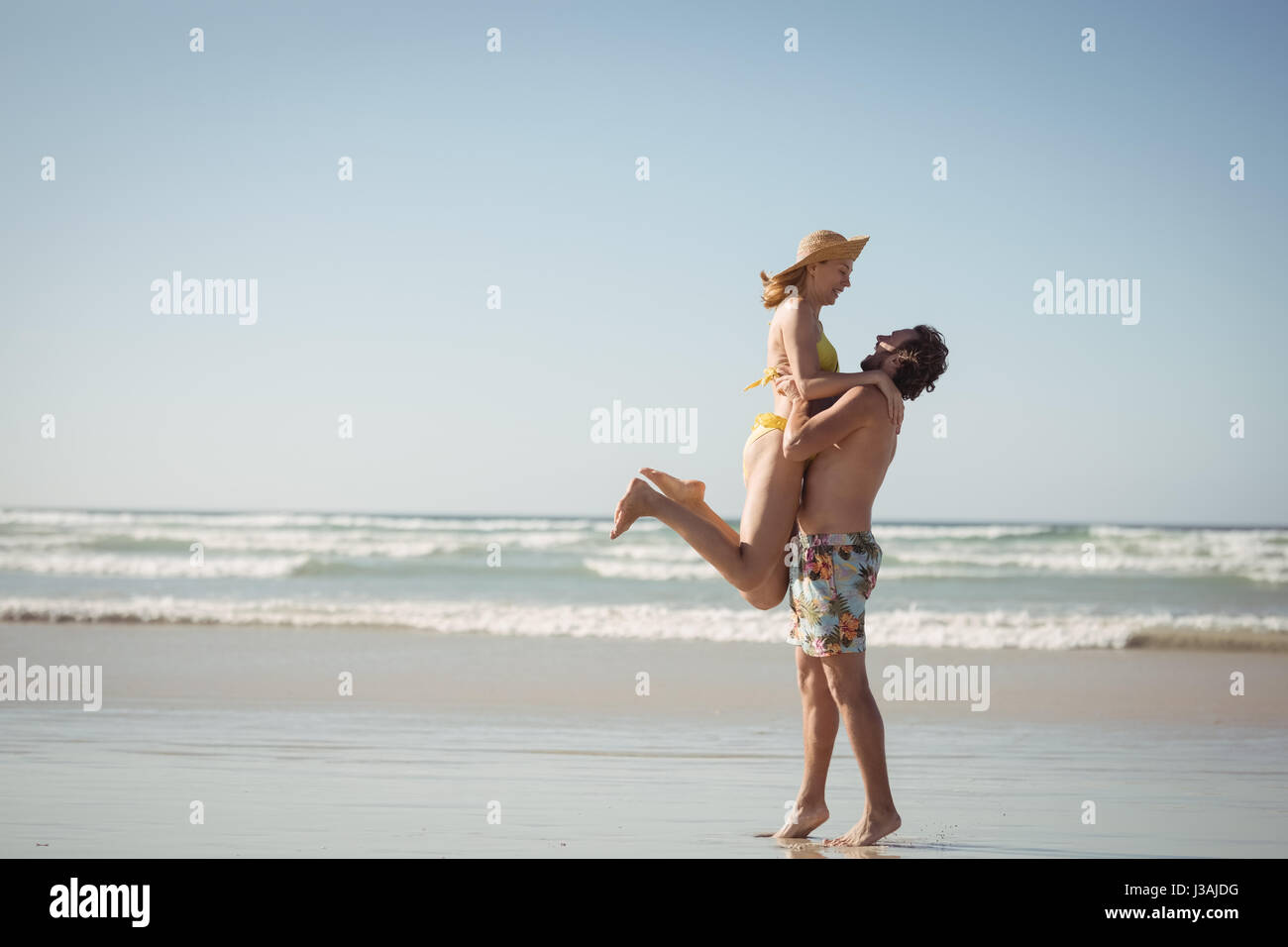 Side view of man lifting woman at beach against clear sky during sunny day - Stock Image