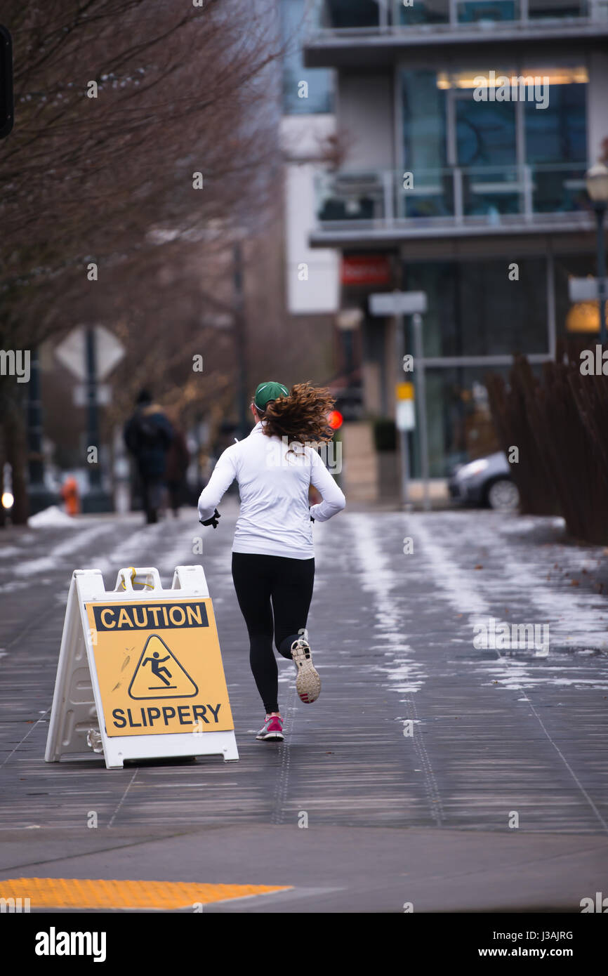A woman likes to run in the street of a modern city of the winter to maintain a good physical condition and recovery - Stock Image