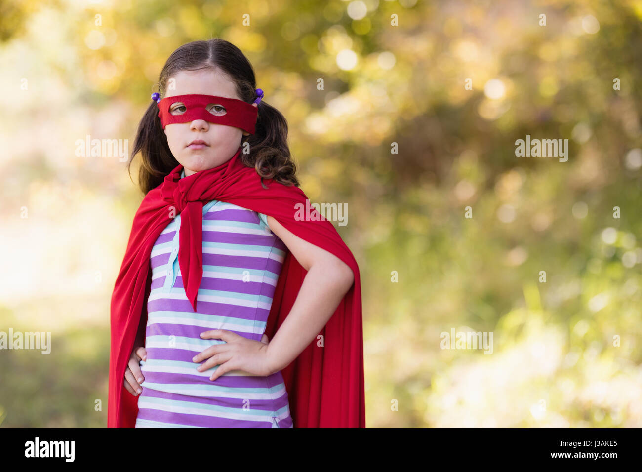Portrait of little girl wearing superhero costume at campsite Stock Photo