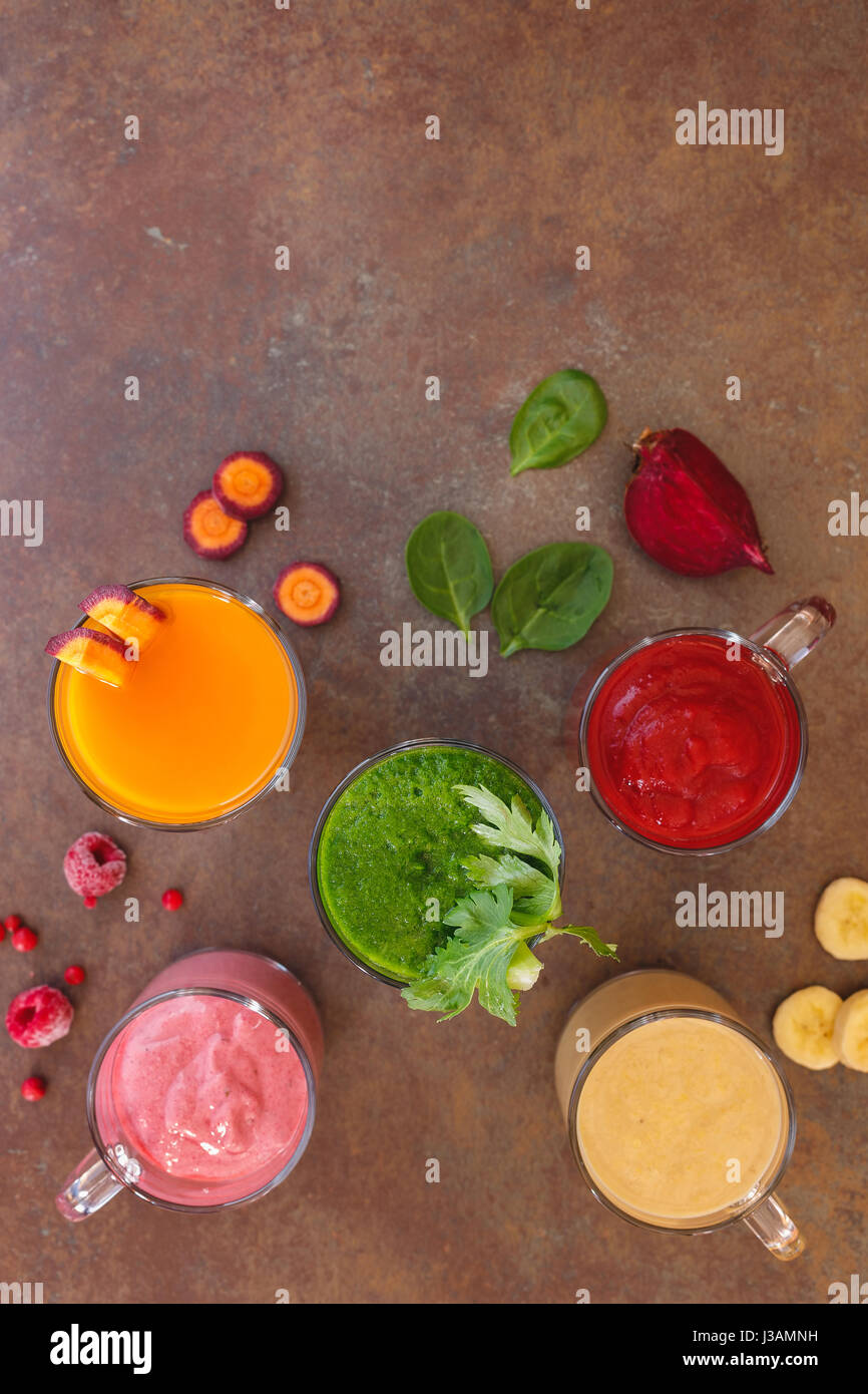 Freshly prepared fruit and vegetable smoothies. Top view, blank space, rustic surface - Stock Image