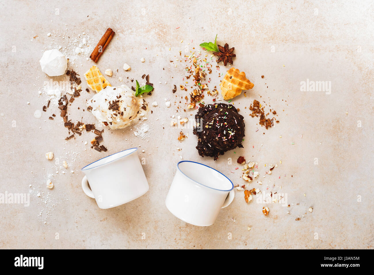 Scoops of ice cream in a variety of delicious and ingredients with two enamel mugs, flat lay Stock Photo