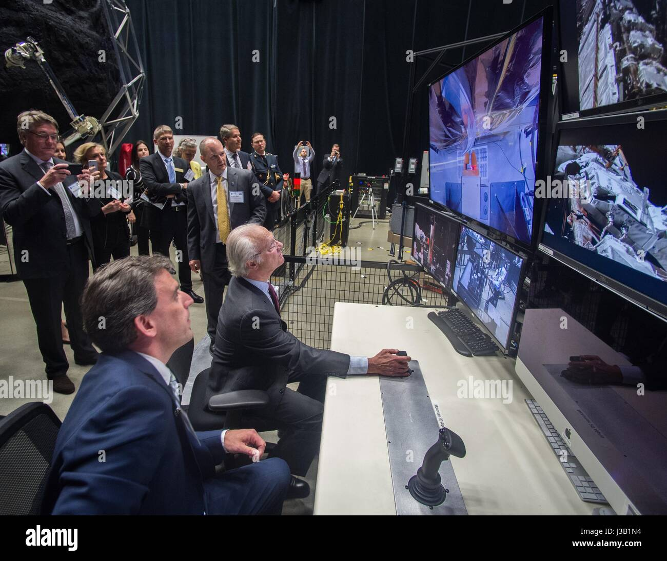 His Majesty The King of Sweden King Carl XVI Gustaf, center, tries his hand at operating a remote robotic arm under - Stock Image