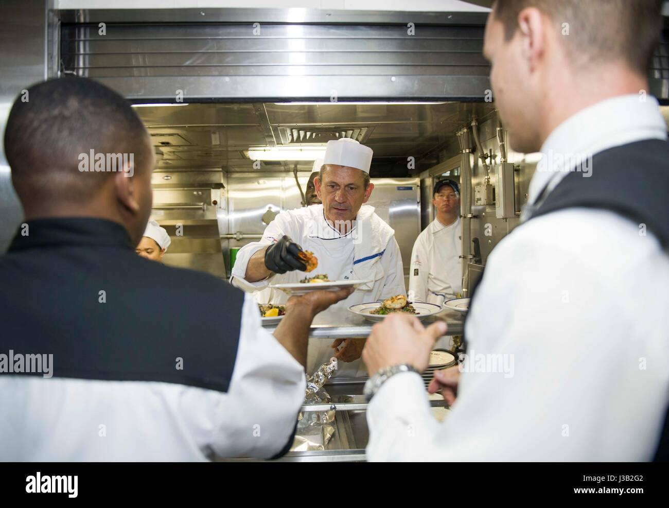 Celebrity Chef Udo Mueller, center, alongside U.S. Navy sailors prepare lunch aboard the amphibious landing dock - Stock Image