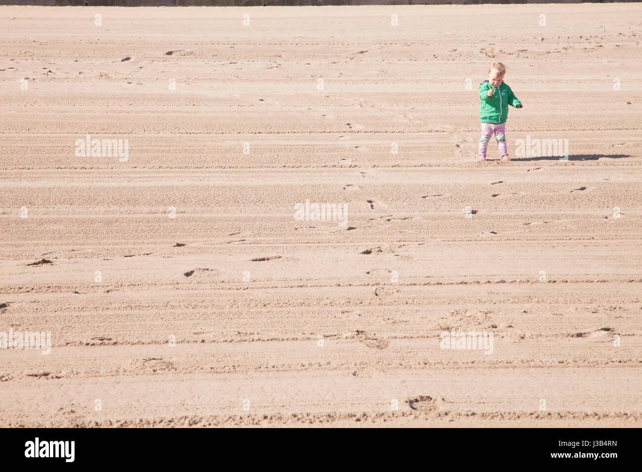 Portobello beach, Edinburgh, UK. 5th May, 2017. Baby girl standing on the sand of Portobello beach on a lovely sunny Stock Photo