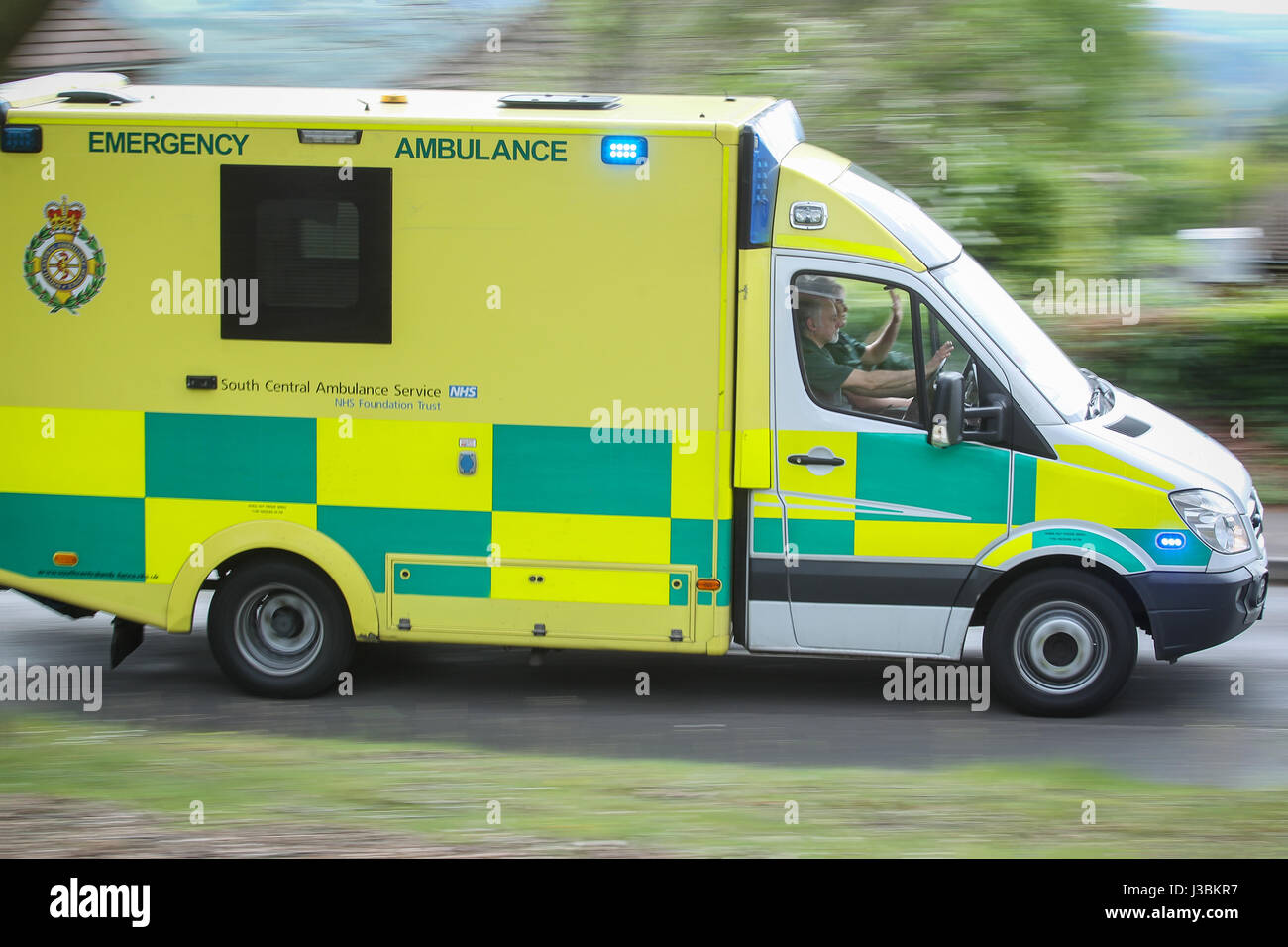 A South Central Ambulance rushing to an emergency with blue lights on - Stock Image