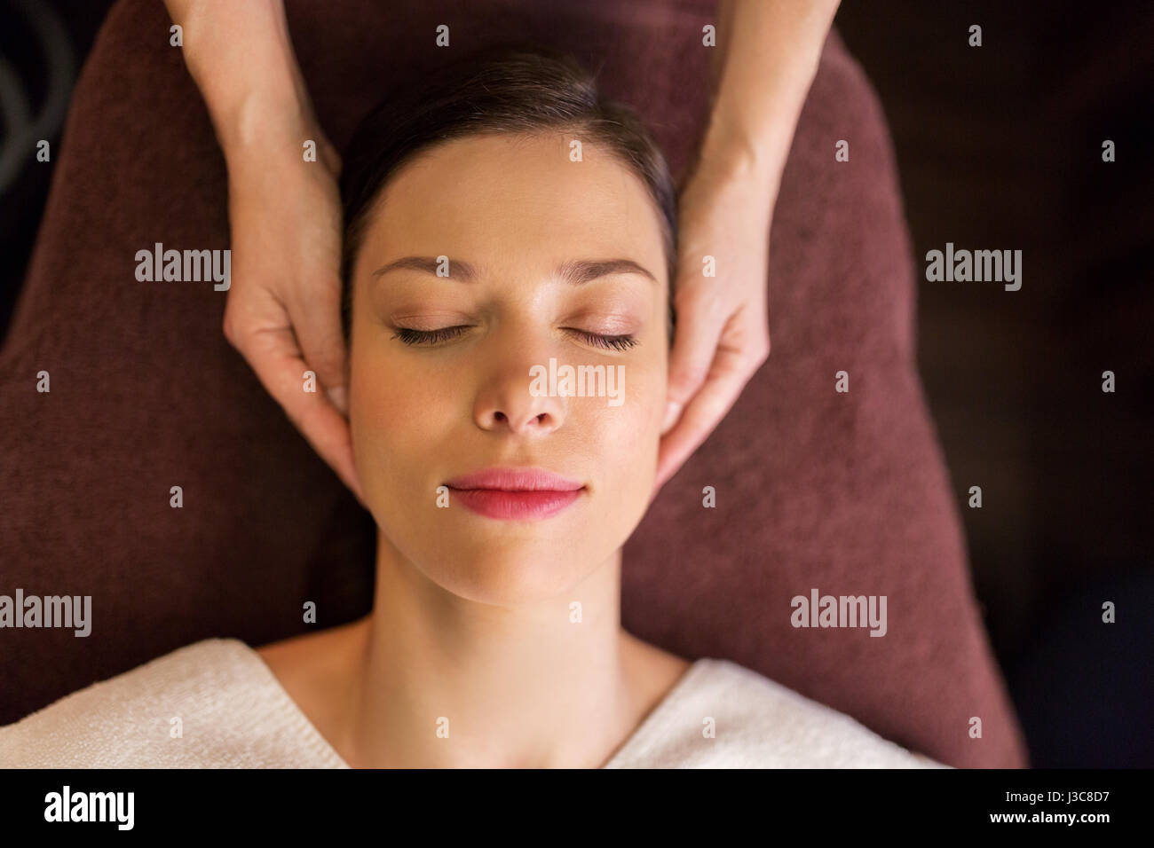 woman having face and head massage at spa - Stock Image