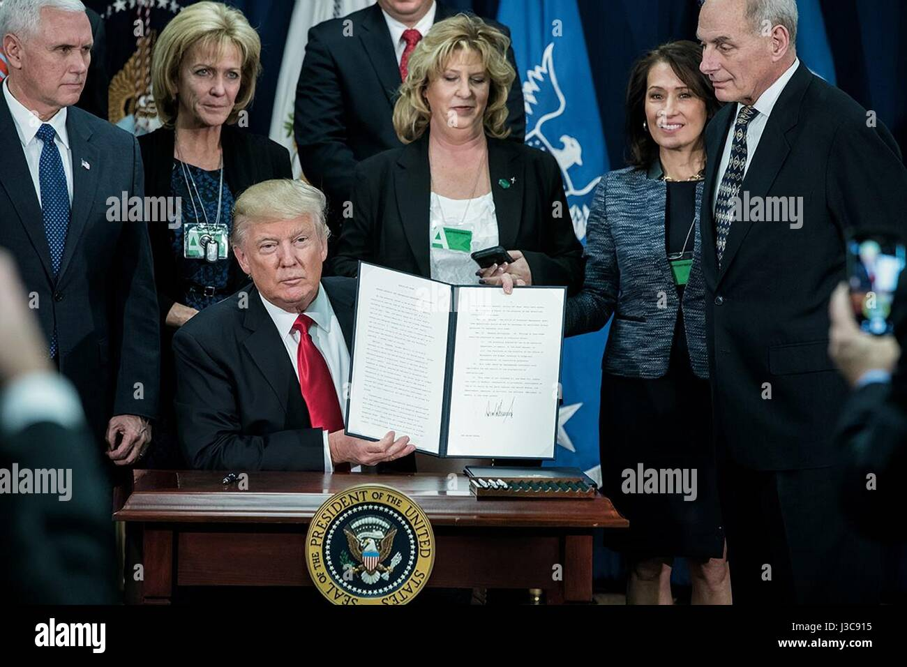 U.S. President Donald Trump holds up the signed Executive Order enhancing border security and immigration enforcement - Stock Image