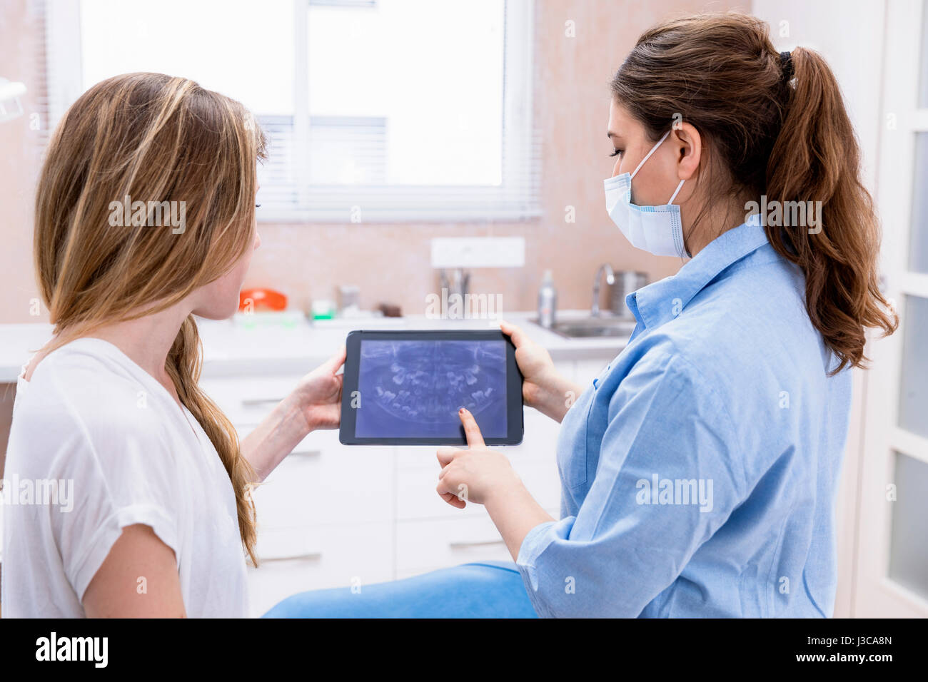 dentist showing teeht x-ray on tablet pc computer to woman patient at dental clinic office - Stock Image