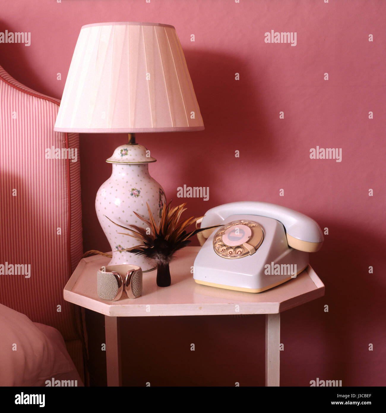 Lamp and rotary dial telephone on bedside table - Stock Image