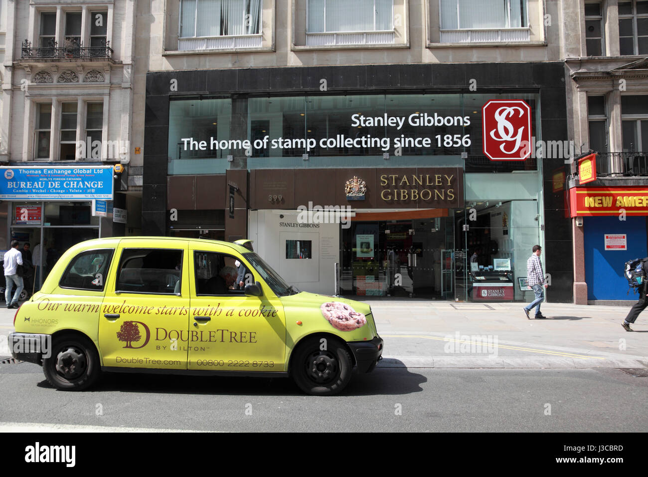 A taxi cab advertising Hilton DoubleTree hotels outside Stanley Gibbons on the Strand, London - Stock Image