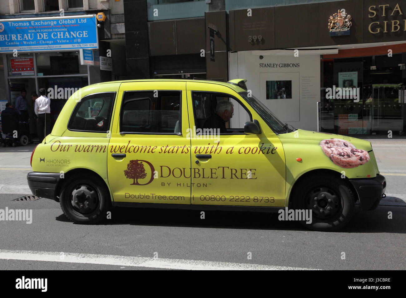 A taxi cab advertising Hilton DoubleTree hotels on the Strand, London - Stock Image