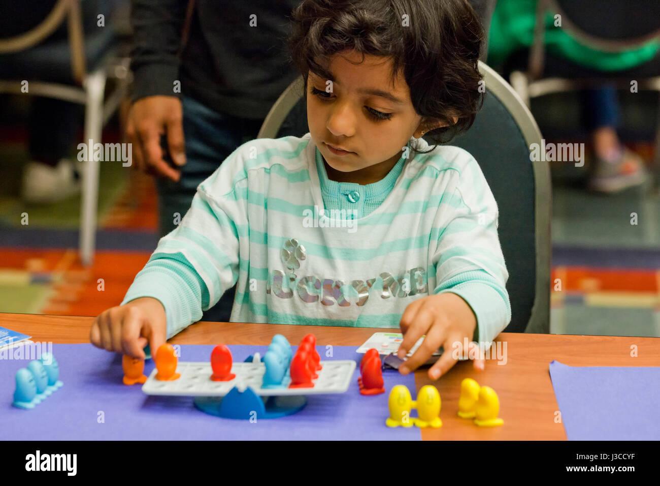 Girl playing Balance Beans board game - USA - Stock Image