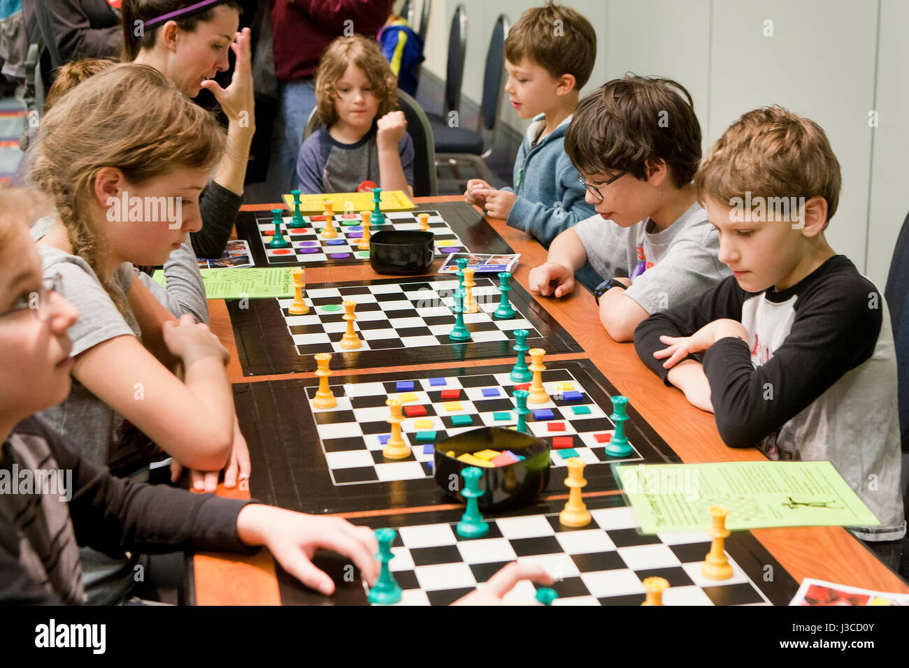 Caucasian American school children playing Game of the Amazons board game - USA - Stock Image