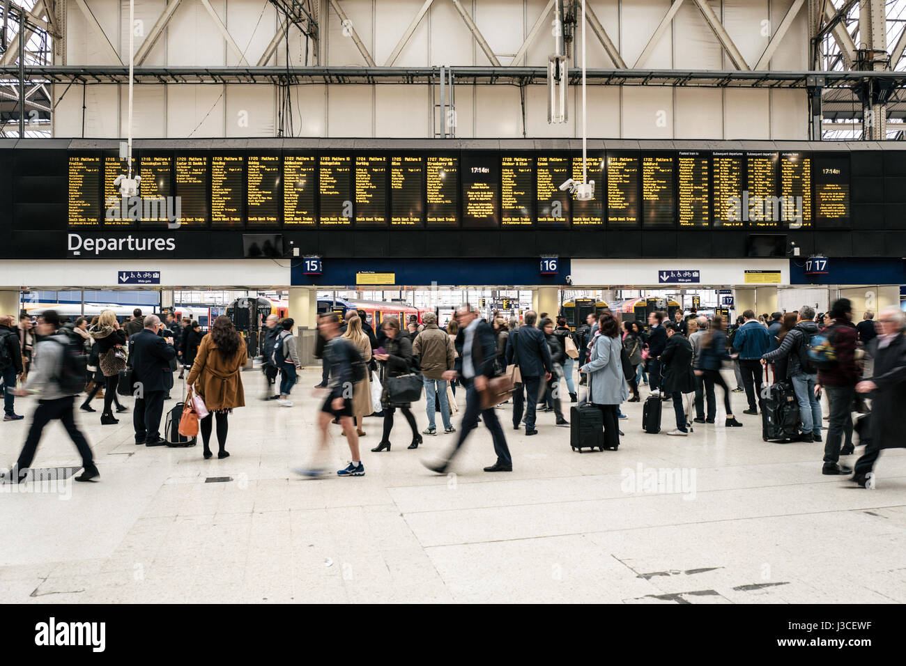 Commuters walk past the departure board in Waterloo Station, central London. - Stock Image