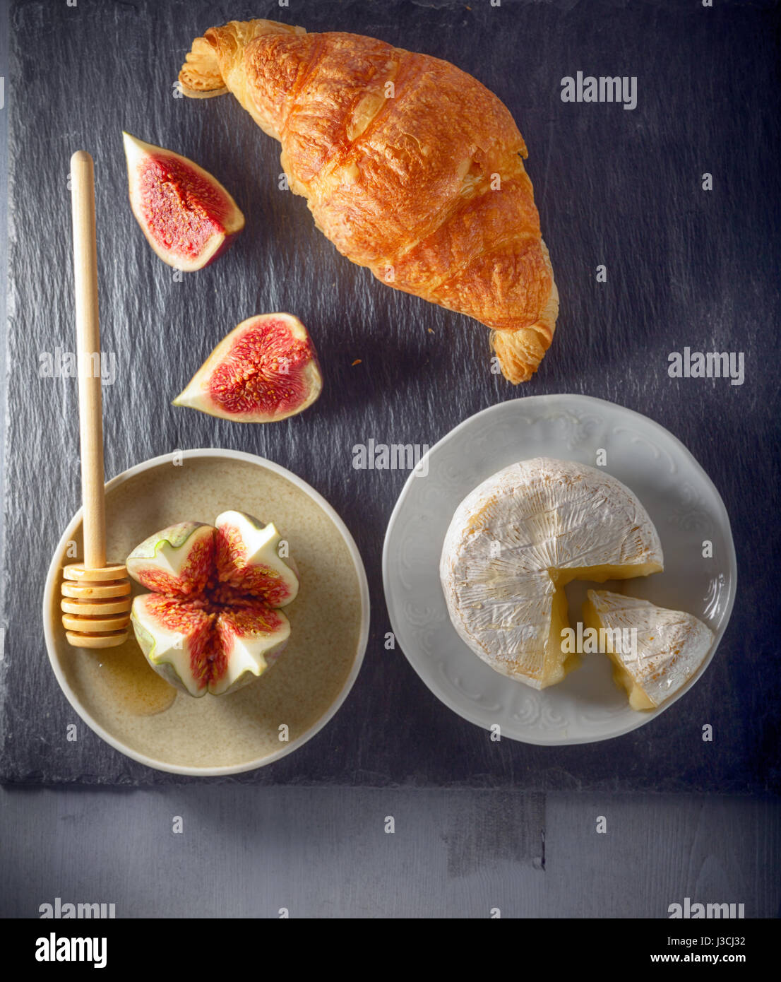 Croissant with soft cheese and figs on a stone plate - Stock Image