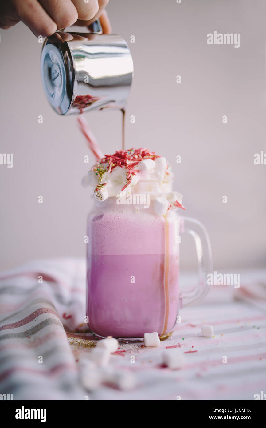 Woman is pouring coffee in cup of colored milk with cream, marshmallow and colorful decoration. Milk shake, cocktaill, - Stock Image