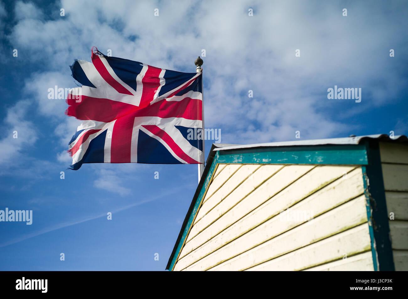 A slightly ragged Union Jack flag mounted on a seaside shed - Stock Image