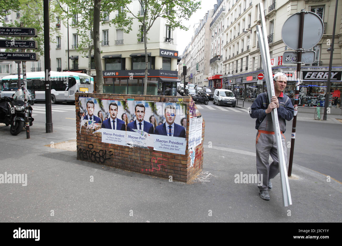 A man walks by election campaign posters of French presidential election candidate for the En Marche ! movement - Stock Image