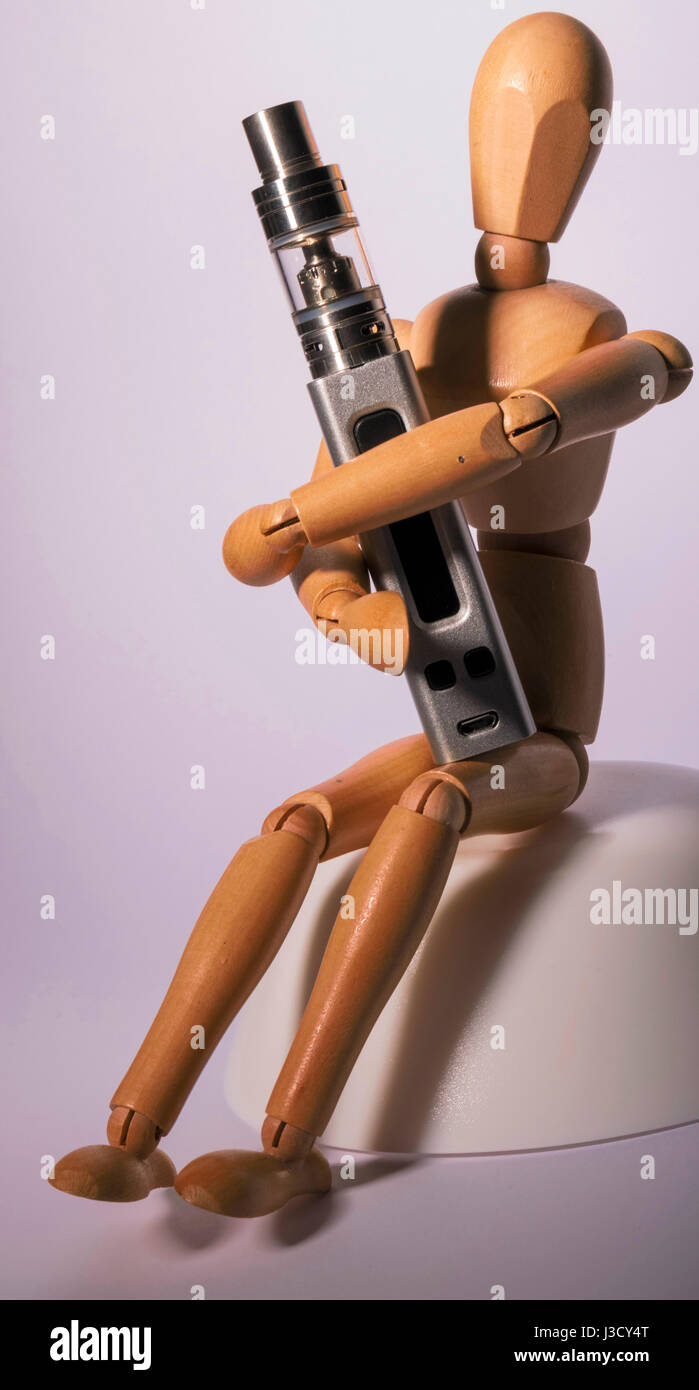 Isolated vaping electronic cigarette hold by a wooden figure. - Stock Image