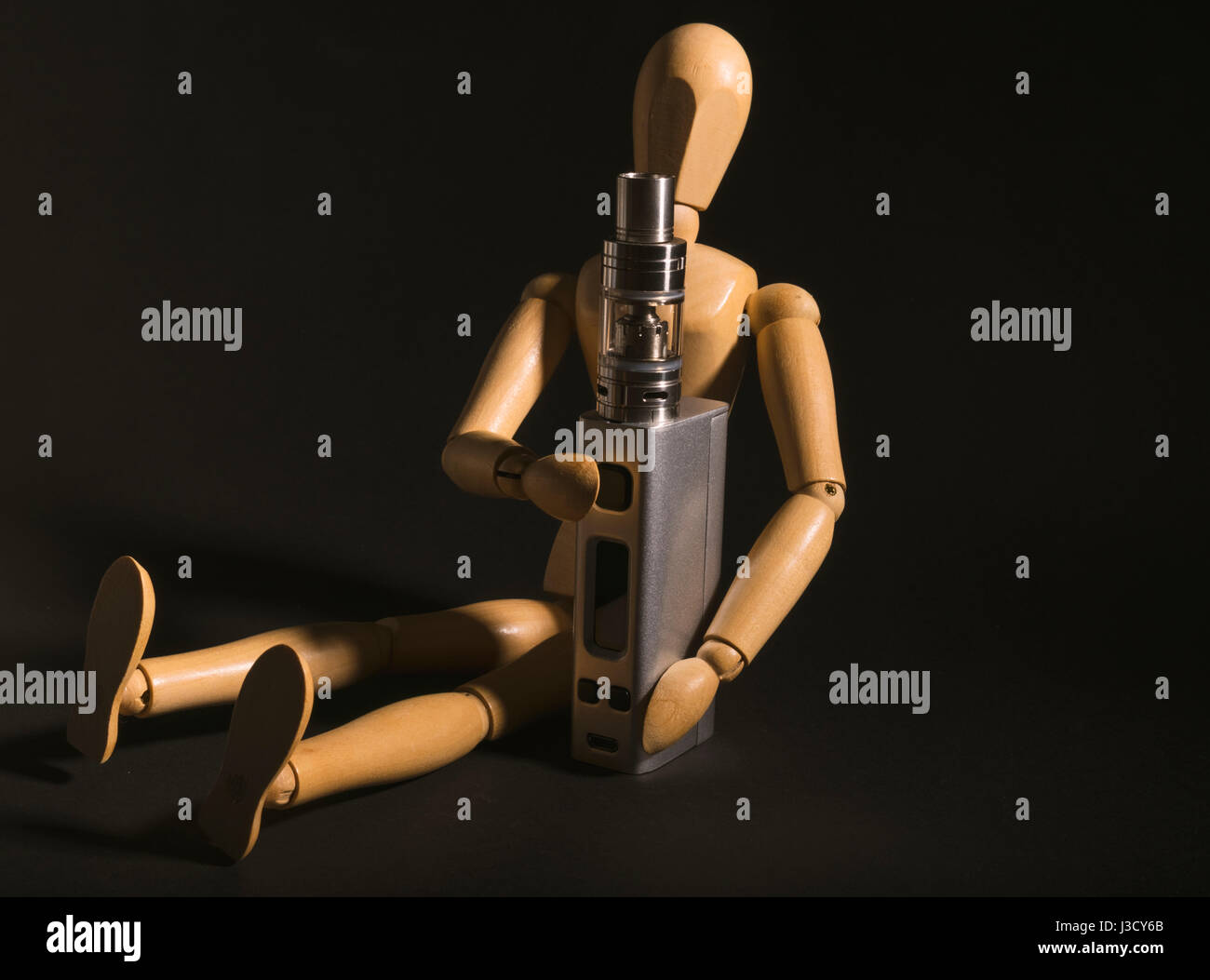 Isolated wooden man holding an electronic device or vaping e cig. - Stock Image