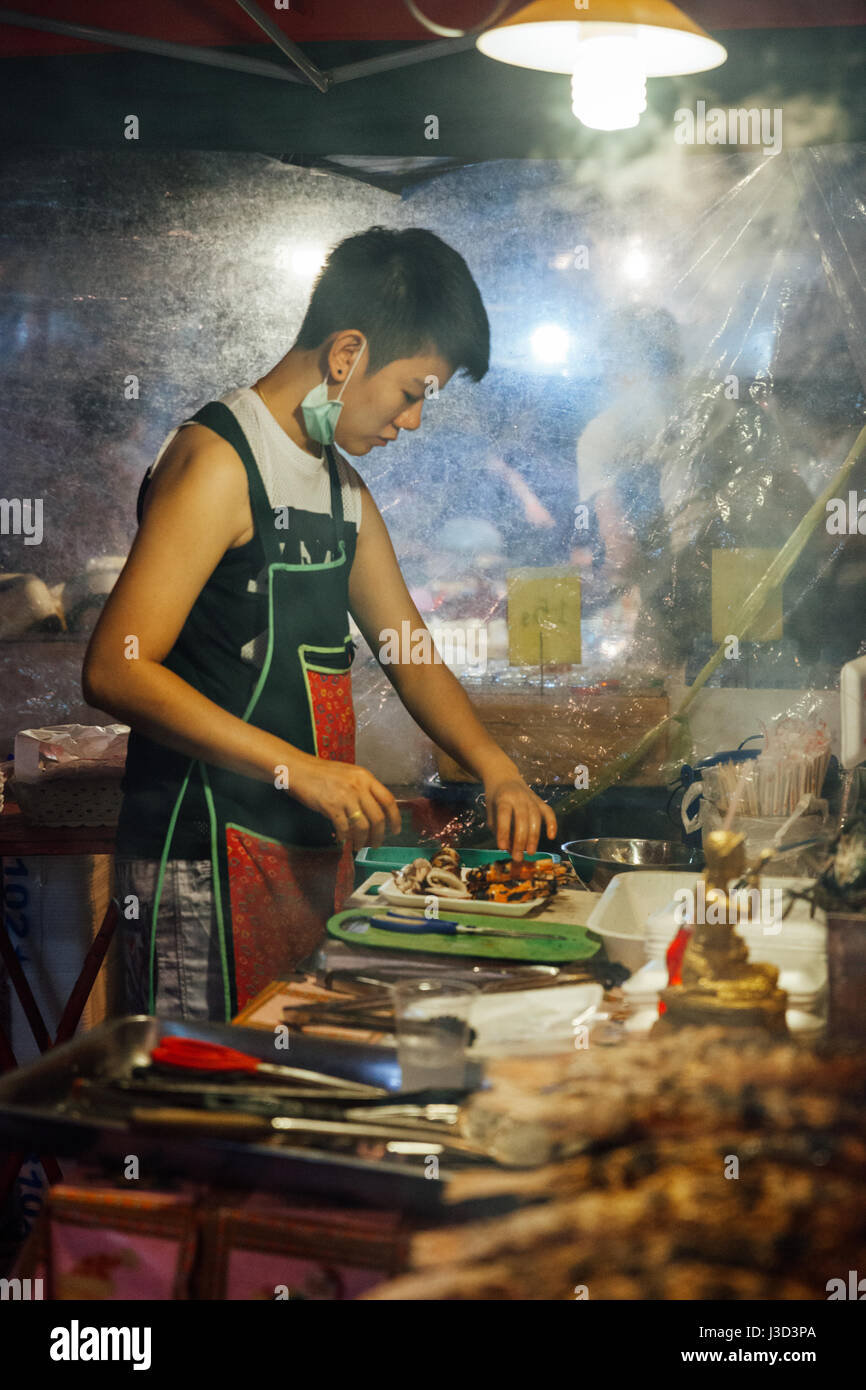 CHIANG MAI, THAILAND - AUGUST 27: Food vendor cooks fish and seafood at the Saturday Night Market (Walking Street) - Stock Image