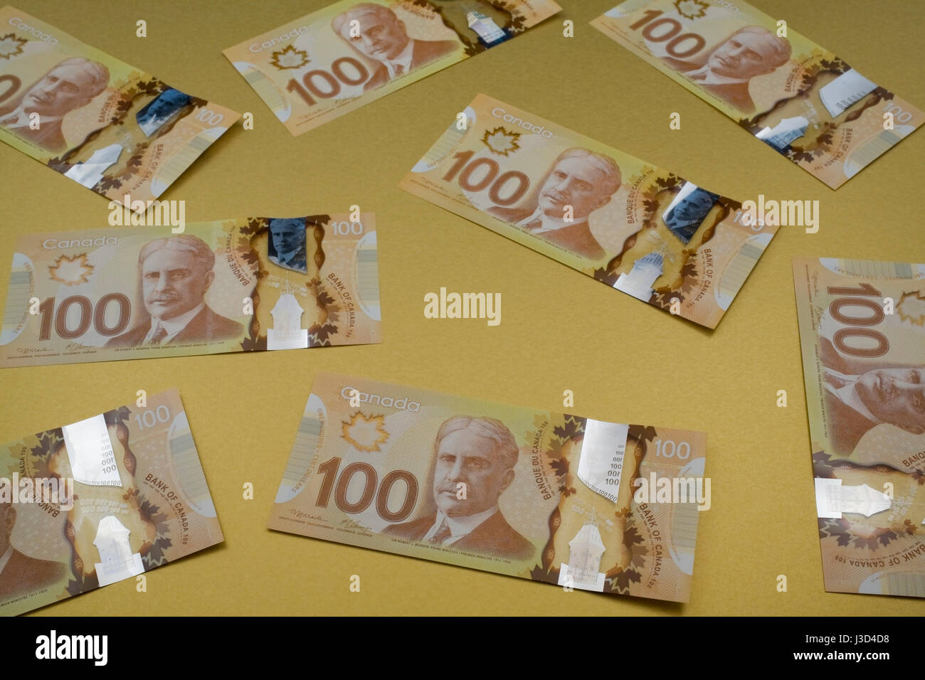 New Canadian 100 dollar bills on a gold background - Stock Image