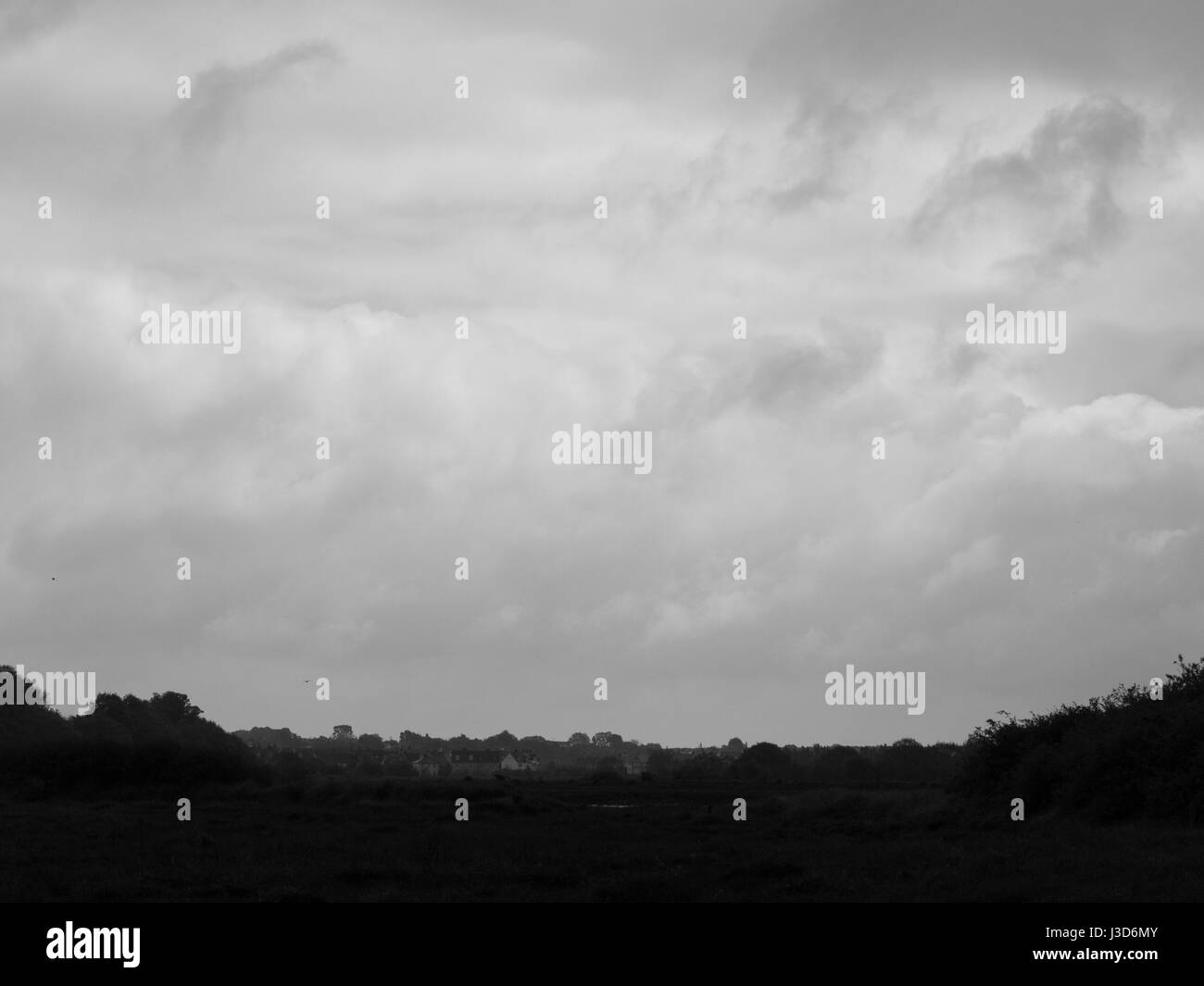 black and white overcast clouds over small town and field dark - Stock Image