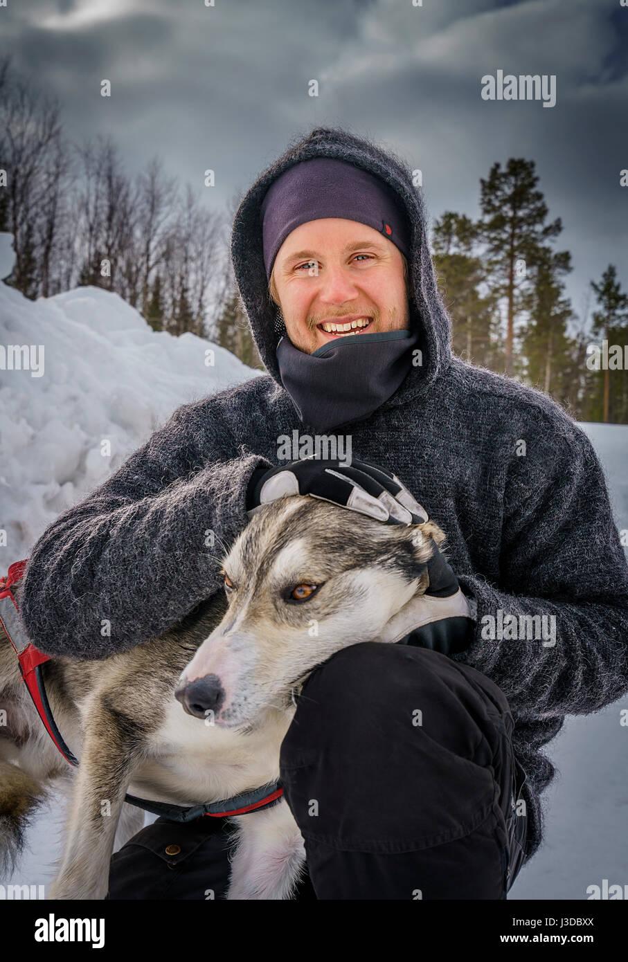 Man with Husky, a sled dog, Swedish Lapland, Sweden - Stock Image