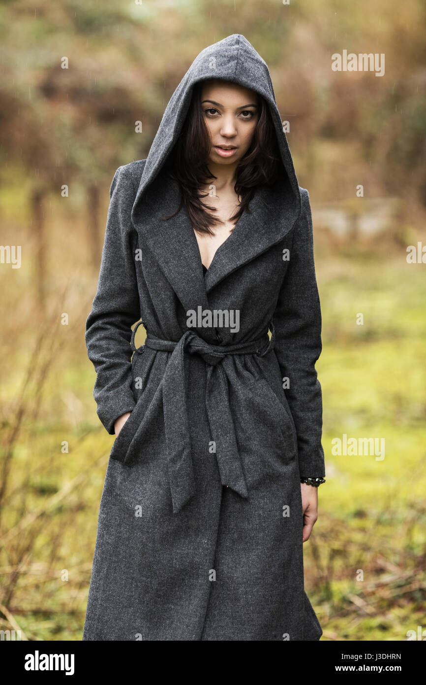 A young woman walking in the countryside dressed in a hooded coat - Stock Image