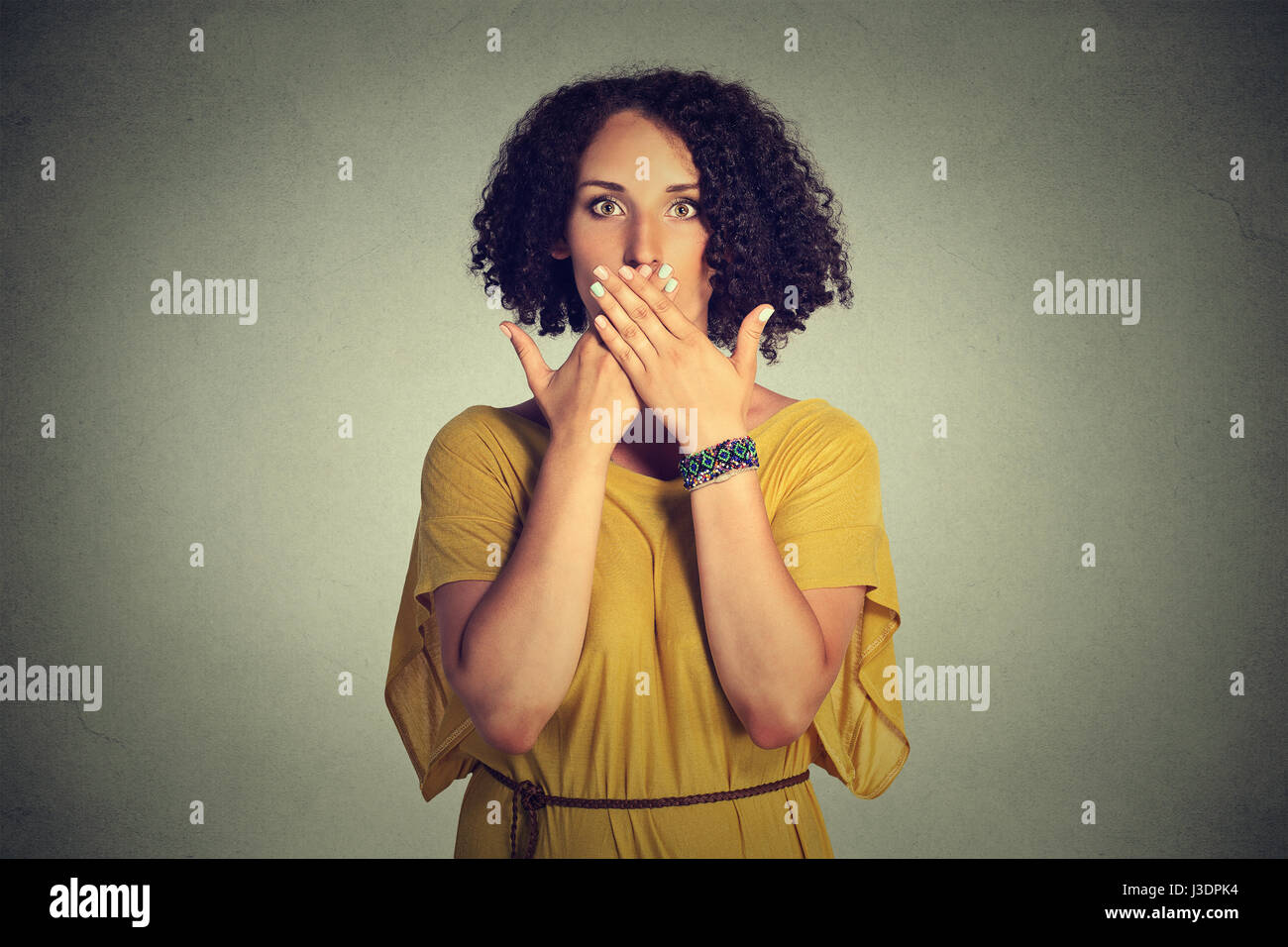 Closeup portrait young woman covering closed mouth with hands. Speak no evil concept isolated on grey wall background. - Stock Image