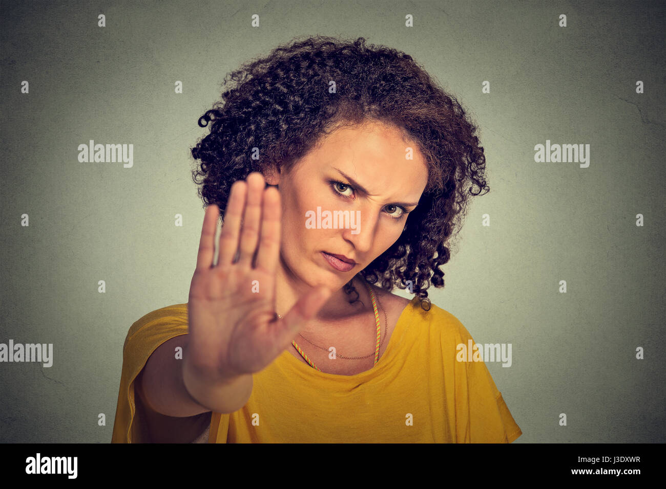 Closeup portrait young annoyed angry woman with bad attitude giving talk to hand gesture with palm outward isolated - Stock Image
