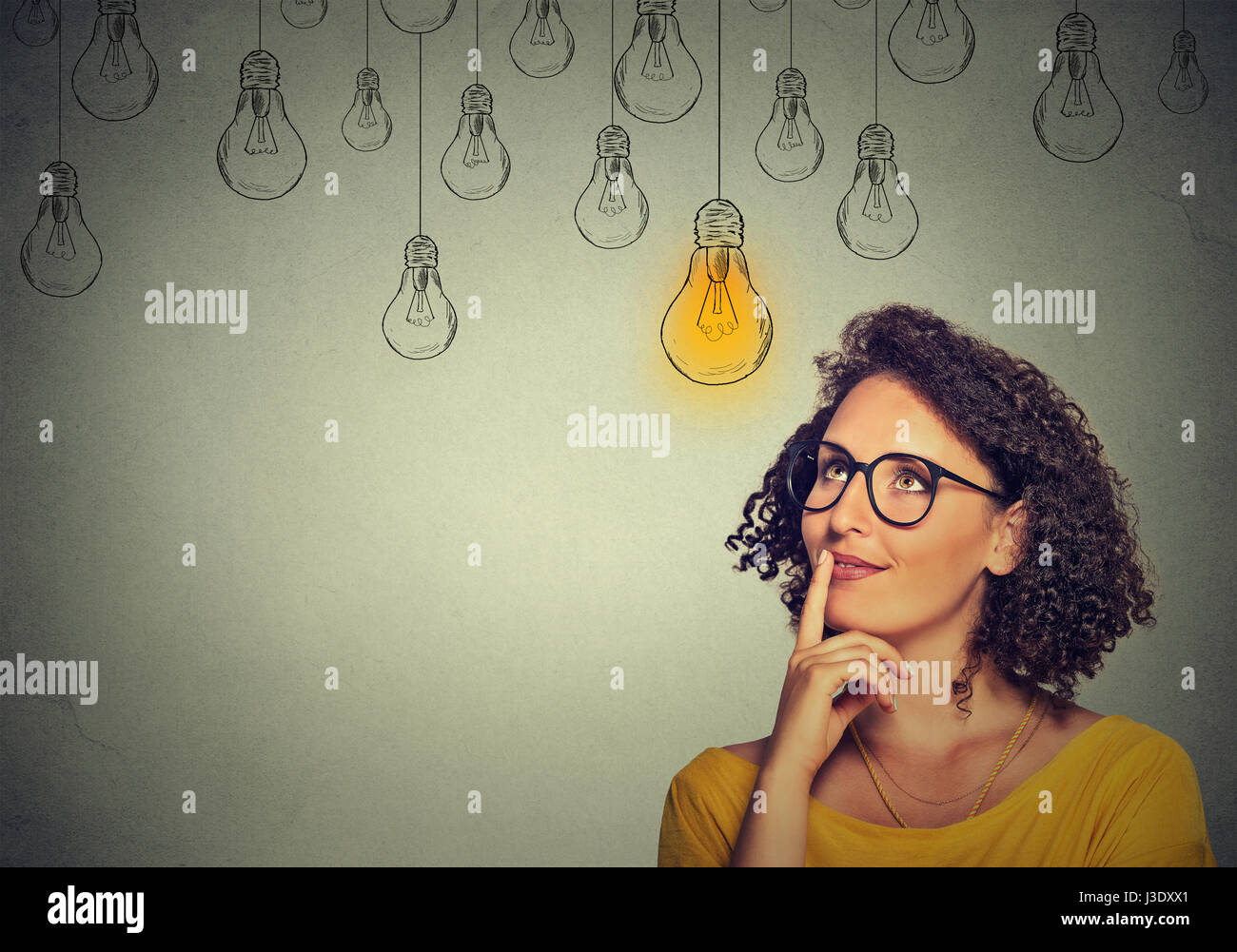 Portrait thinking woman in glasses looking up with light idea bulb above head isolated on gray wall background - Stock Image